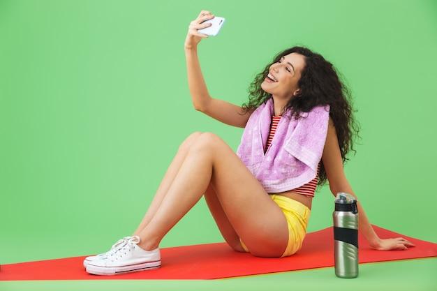 녹색 벽에서 운동한 후 피트니스 매트에 앉아 셀카 사진을 찍는 목에 수건을 두른 운동복을 입은 20대 예쁜 여성의 초상화