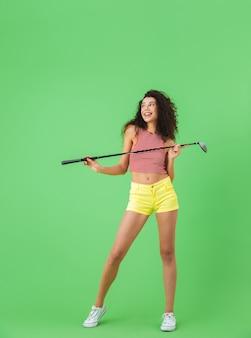 녹색 벽에 서서 클럽을 잡고 골프를 치는 여름 옷을 입은 예쁜 20대 여성의 초상화