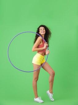 Портрет красивой женщины 20-х годов в летней одежде, делающей упражнения с обручем во время тренировки на зеленой стене