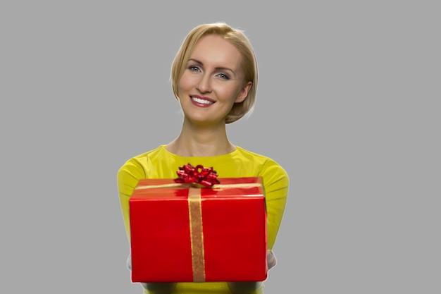 누군가에게 선물 상자를 나눠 예쁜 여자의 초상화. 회색 배경에 포장 된 선물 상자를 제공하는 아름 다운 웃는 여자.