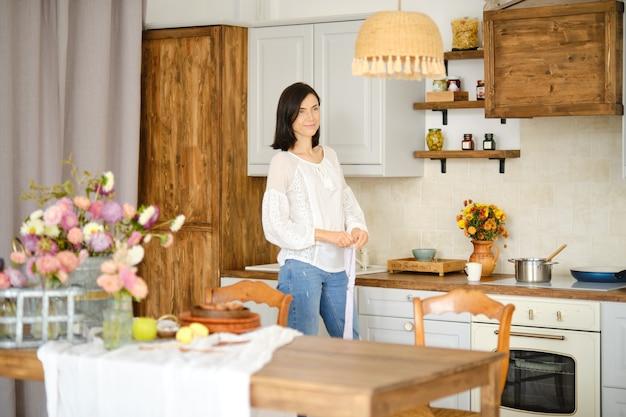 Портрет красивой женщины в повседневной одежде на кухне с чашкой кофе в руке