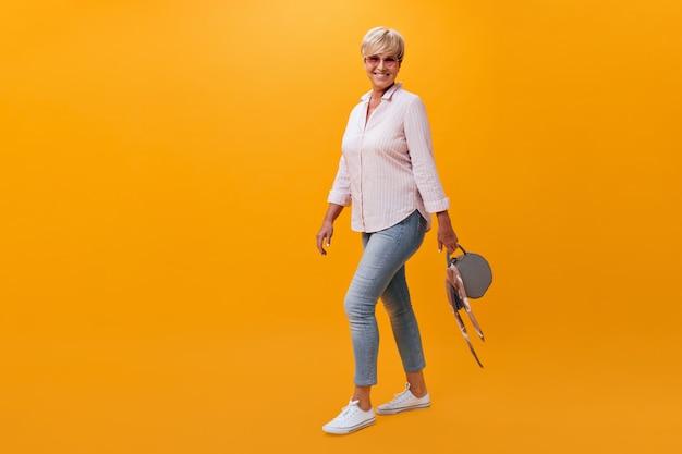 Портрет красивой женщины в джинсах и рубашке, позирующей с сумкой на оранжевом фоне