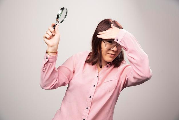 虫眼鏡を持ったピンクの服を着たきれいな女性のポートレート。高品質の写真