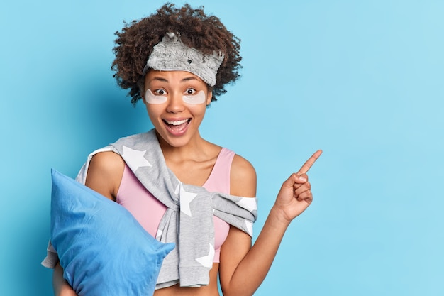 きれいな女性の肖像画は、コピースペースでパジャマの衣装を着て柔らかい枕を保持していることを示しています青い壁の上に隔離された幸せな表情はsleepmaskを着ています。あなたのプロモーションはここにあります。
