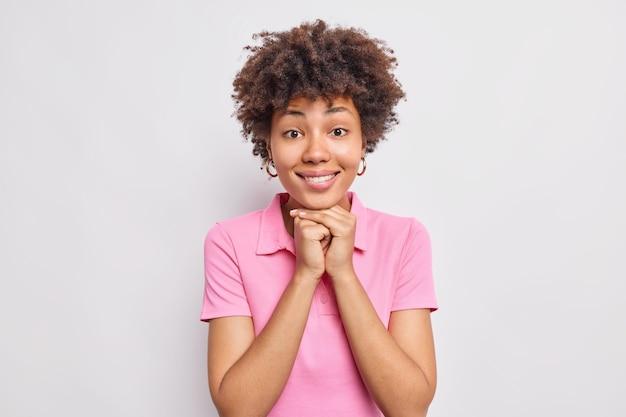 예쁜 여성의 초상화는 흰 벽에 격리된 캐주얼한 분홍색 티셔츠를 입고 즐겁게 턱 미소를 짓고 있습니다.