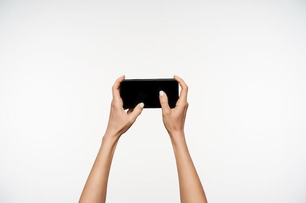 携帯電話を持ち、画面に親指を置いたまま、白いマニキュアを上げて、白い上に立っているきれいな女性の手の肖像画