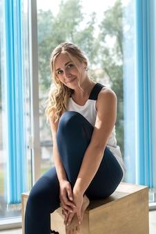 Портрет красивой женщины, сидящей и отдыхающей на деревянном кубе после тренировки в тренажерном зале