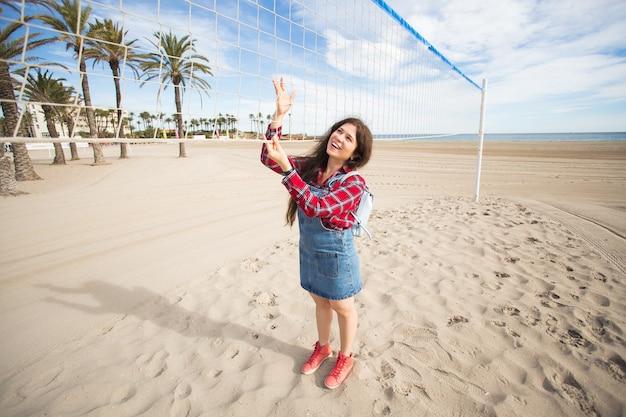 暑い夏の日にバレーボールネットの近くの砂浜に立っているきれいな女性の観光客の肖像画。