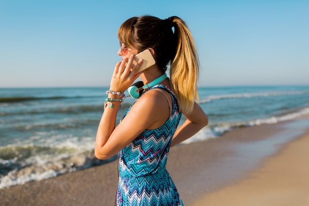 太陽が降り注ぐビーチでスマートフォンを使用してきれいな女性の肖像画