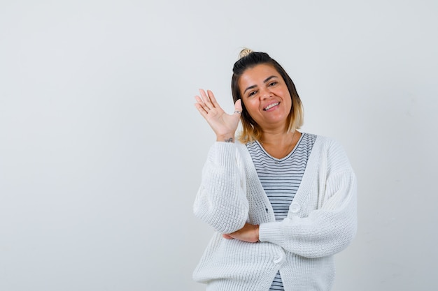 Портрет красивой женщины, махающей рукой для приветствия в футболке, кардигане и веселого вида спереди