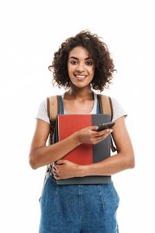 Портрет красивой женщины в рюкзаке с тетрадями и мобильным телефоном, изолированными над белой стеной