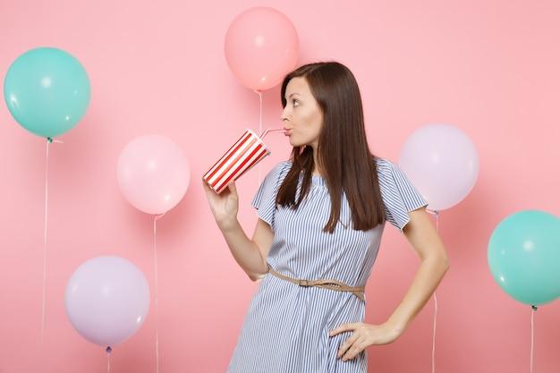 파스텔 핑크색 배경에 화려한 공기 풍선이 달린 플라스틱 컵에서 콜라나 탄산음료를 옆으로 바라보며 파란 드레스를 입은 예쁜 여성의 초상화. 생일 휴가 파티, 사람들은 진심 어린 감정.