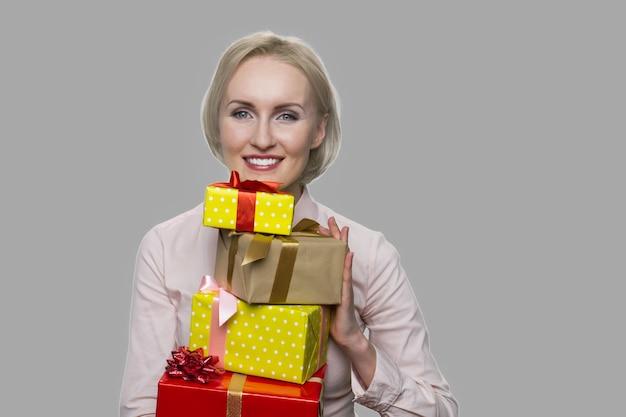 선물 상자 더미와 함께 예쁜 여자의 초상화. 선물 상자 스택과 함께 행복 한 흥분된 소녀입니다. 여성의 날 선물. 좋은 일에 대한 보상.