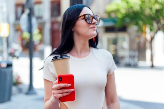 테이크아웃 커피를 마시는 도시에서 선글라스를 낀 예쁜 여성의 초상화