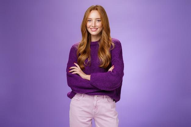 Портрет довольно молодой и счастливой рыжей девушки 20-х годов в фиолетовом свитере, держащей руки, скрещенные над телом, широко улыбаясь, чувствуя себя уверенно, продвигая проект с уверенностью через фиолетовую стену.