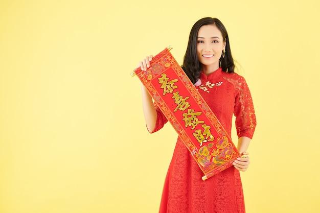 Портрет довольно молодой азиатской женщины, держащей куплеты с наилучшими пожеланиями как украшение для празднования китайского нового года