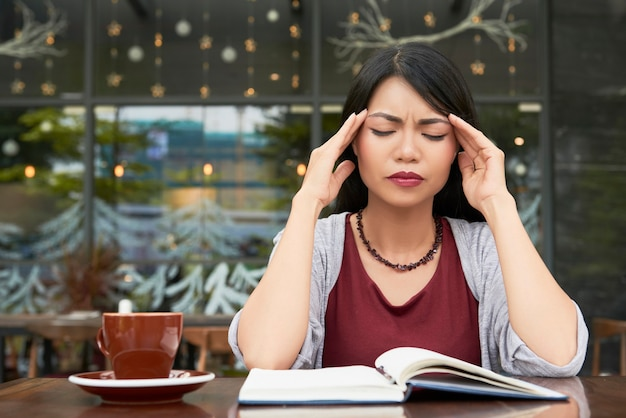 Портрет довольно молодой азиатской женщины, страдающей от сильной головной боли при попытке поработать в кафе