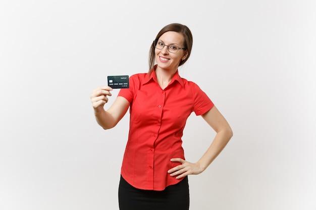 Портрет довольно молодой женщины-учителя бизнеса в красных очках юбки рубашки, держащей банковскую карту cedit, безналичные деньги, изолированные на белом фоне. обучение преподаванию в концепции университета средней школы.