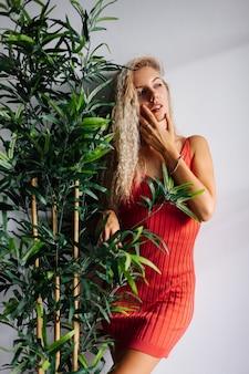 빨간 미니 드레스에 가벼운 자연 메이크업으로 꽤 젊은 백인 여자의 초상화