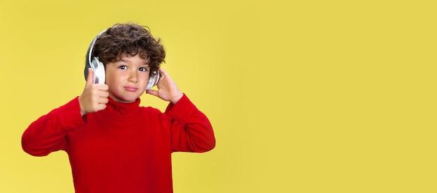Портрет довольно молодого кудрявого мальчика в красной одежде на желтом фоне студии. детство, выражение, образование, концепция развлечения.