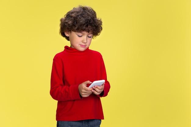 黄色のスタジオの背景に赤い摩耗でかなり若い巻き毛の少年の肖像画。子供の頃、表現、教育、楽しいコンセプト。
