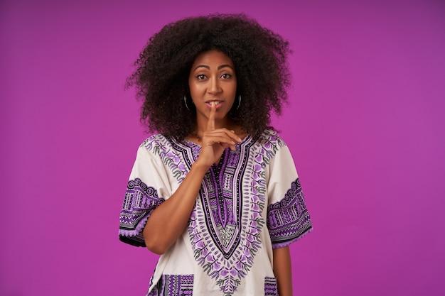 白い模様のシャツを着て、人差し指を唇につけ、沈黙を保つように求め、紫色でポーズをとる、黒い肌のかなり若い巻き毛の女性の肖像画