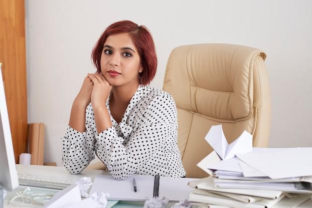 ドキュメントとレポートとオフィスの机に座っているかなり若い女性起業家の肖像画