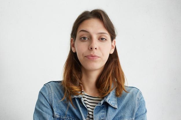 Портрет довольно молодой женщины, поднимающей бровь с чудом, одетым в изолированную джинсовую куртку. подозрительная женщина, хмурясь.