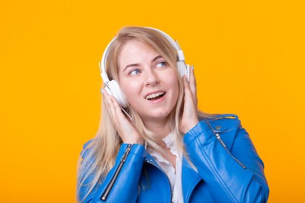 青い革のジャケットとスマートフォンを保持しているかなり若い女の子の金髪の女子学生の肖像画