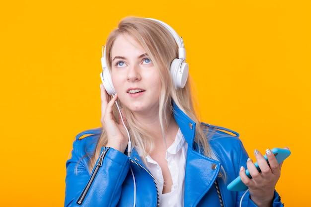 Портрет красивой молодой девушки блондинки студентки, держащей смартфон с синей кожаной курткой