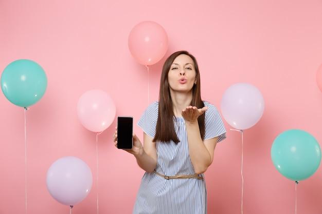 カラフルな気球とパステルピンクの背景にエアキスを送信する空白の空の画面で携帯電話を保持している青いドレスのかなり若い幸せな女性の肖像画。誕生日の休日のパーティーのコンセプト。