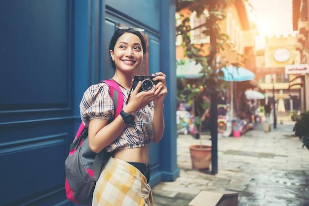カメラで街で楽しい、かなり若いhipster女性の肖像画