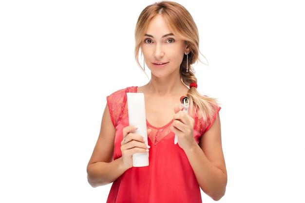 Портрет довольно молодой леди, стоя с кремом и роликом для массажа лица, изолированные на белом фоне. скопируйте пространство. концепция терапии массаж лица