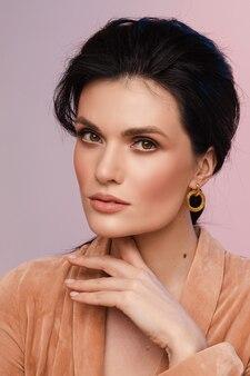 턱 근처에 손을 잡고 세련된 스타일링으로 예쁜 아가씨의 초상화. 패션 컨셉