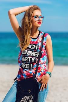 ブロンドの髪と熱帯の楽園のビーチでポーズのサングラスを持つかなり若い官能的な見事な女性の肖像画