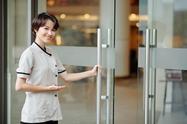 ガラスのドアを開けて、中にゲストを招待するかなり若いベトナムの女性ホテル労働者の肖像画