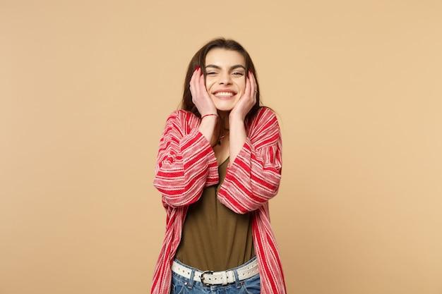 スタジオでパステルベージュの背景に分離された頬に手を置いて、カメラを探しているカジュアルな服を着たかなり若い女性の肖像画。人々の誠実な感情、ライフスタイルのコンセプト。コピースペースをモックアップします。