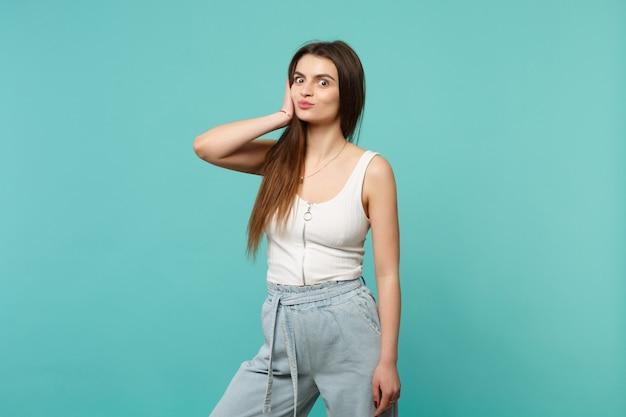 가벼운 캐주얼 옷을 입고 카메라를 찾고 있는 예쁜 젊은 여성의 초상화, 뺨을 불고, 푸른 청록색 벽 배경에 격리된 입술. 사람들은 진심 어린 감정, 라이프 스타일 개념입니다. 복사 공간을 비웃습니다.