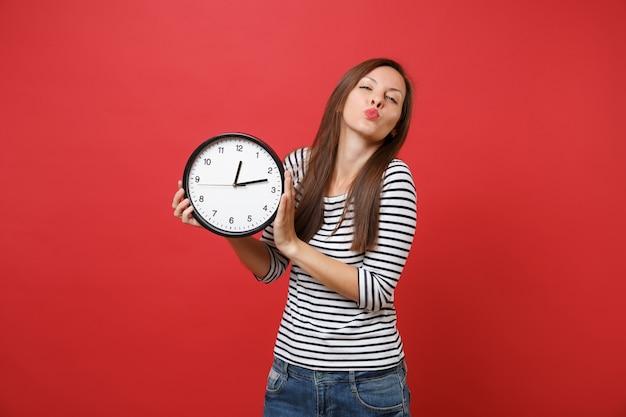 Портрет красивой молодой женщины в полосатой одежде, дует поцелуями, посылает воздушный поцелуй, держа круглые часы, изолированные на ярко-красном фоне. люди искренние эмоции, концепция образа жизни. копируйте пространство для копирования.