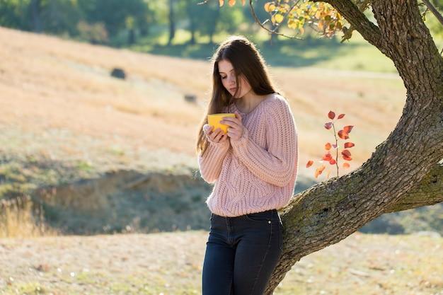 黄金の秋の森に立っているスタイリッシュなニットセーターのかなり若い女性の肖像画