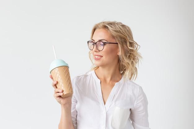 예쁜 젊은 여자의 초상화는 흰 벽에 스무디를 마시고