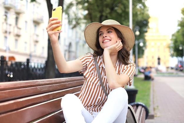 Портрет довольно молодой женщины, делающей селфи по телефону, сидя на скамейке на городской улице.