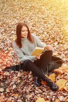 Портрет красивой молодой женщины славянской внешности в повседневной одежде осенью, читающей книгу на поляне. симпатичная модель, прогулки в парке в золотой осени на фоне природы. копировать пространство