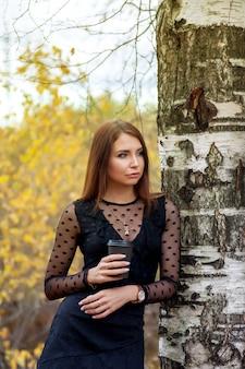 가을 공원과 물 연못의 배경에 대해 자작 나무 옆에 서있는 검은 드레스와 가을에 커피 잔에 슬라브 모양의 예쁜 젊은 여자의 초상화