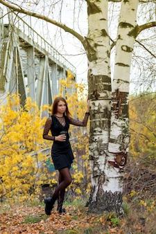 暗いドレスと秋のコーヒーのガラスのスラブの外観のかなり若い女性の肖像画、背景に対して白樺の木の横に立って