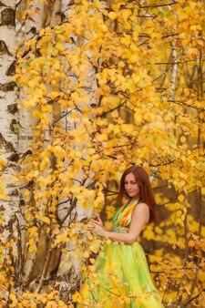 Портрет красивой молодой женщины славянской внешности в желтом платье осенью, стоит в лесу с березками