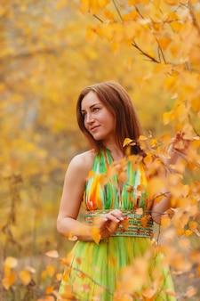 Портрет красивой молодой женщины славянской внешности в желтом платье осенью, прогулка в лесу