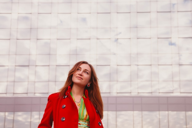 Портрет красивой молодой женщины славянской внешности в желтом платье и красном пальто. фасад делового здания