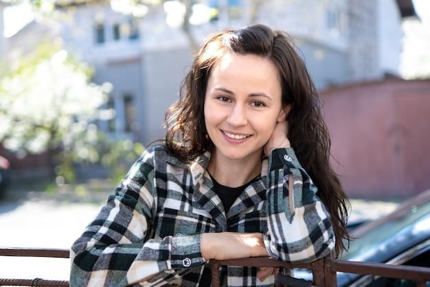 春の晴れた日に屋外で楽しくリラックスして笑っているかなり若い女性の肖像画。