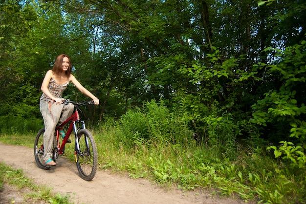 Портрет красивой молодой женщины с велосипедом в парке улыбается - открытый
